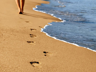 Человек идет по пляжу
