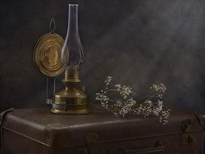 Старинная лампа стоящая на чемодане