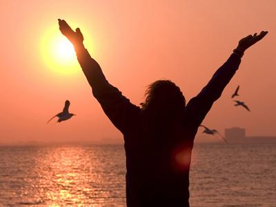 Девушка на берегу моря с поднятыми вверх руками в знак благодарности