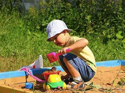 Малыш играет в песочнице в игру База денег