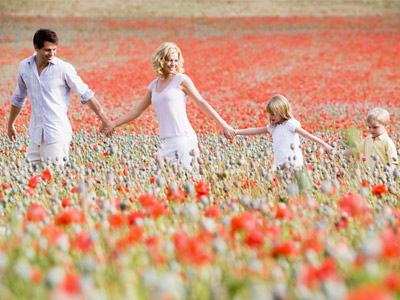 Семья, взявшись за руки, идут по полю из цветов