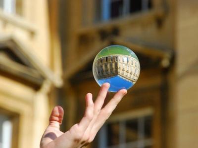 Жонглёр держит на пальцах стеклянный шар