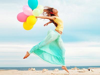 Девушка с воздушными шарами бежит по берегу