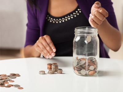 Девушка складывает в банку монеты
