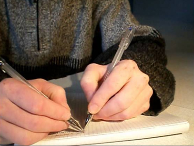 Человек пишет ответы на вопросы двумя руками