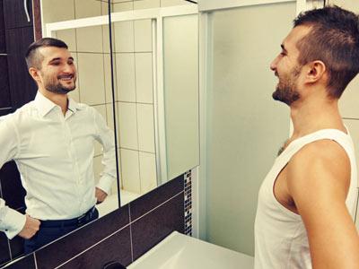 Мужчина смотрит на себя в зеркало и видит сея успешным человеком